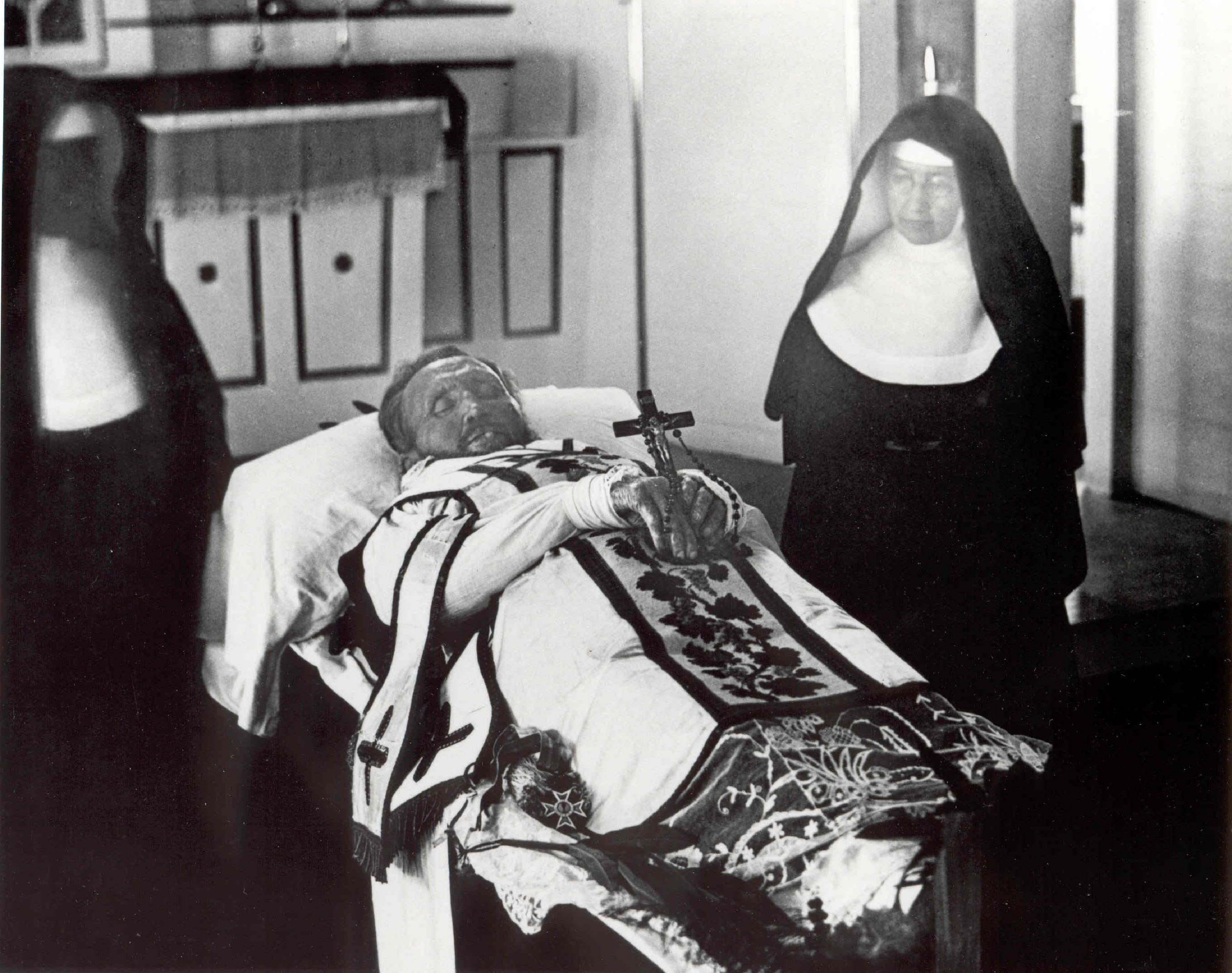 Father_Damien_on_his_funeral_bier_with_Mother_Marianne_Cope_by_his_side
